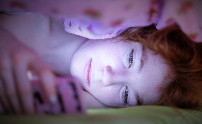 Ilustrasi Wanita lihat smartphone dalam selimut /Ilustrasi Nusantaranews Healt via Rex Features