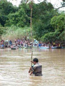 Salah Seorang sedang menancapkan kayu rambutan hutan disaksikan beberapa warga di bibir sungai. Foto: Addy Santri/Nusantaranews