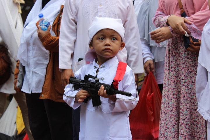 Anak Kecil tampak Sedang membawa pistol mainan dalam aksi 4 November. Foto Andika/Nusantaranews