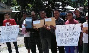 Warga Ponorogo tolak pilkades dengan kirim surat kepada Jokowi dan bentangkan poster protes. Foto Muh Nurcholis/Nusantaranews