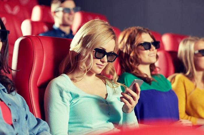 Wanita Melinial asik nonton sesuatu di smartphonenya ketika sedang nonton di bioskop | Polygon