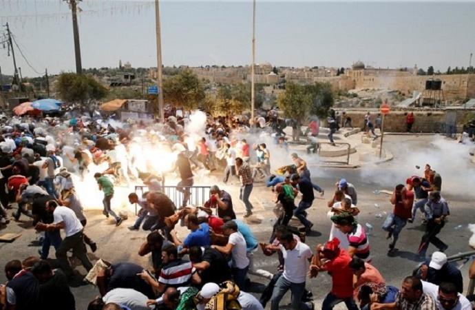 Warga Palestina bereaksi setelah gas air mata yang ditembak oleh pasukan Israel setelah shalat Jumat di sebuah jalan di luar kota tua Yerusalem pada 21 Juli 2017. (Foto: Reuters/Ammar Awad)
