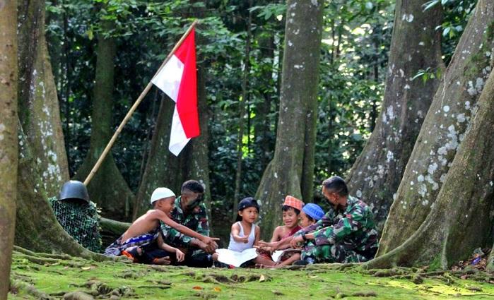 Prajurit TNI bersama anak-anak di bawah naungan Merah Putih, (Foto: Yonif 315/Garuda)