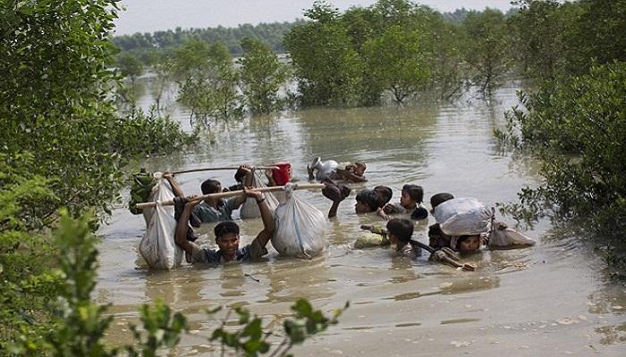 Keluarga Rohingya sampai di perbatasan Bangladesh setelah menyeberangi sungai Naf, yang membentuk perbatasan dengan Myanmmar, di daerah Teknaf Cox's Bazar. (Foto: AP)