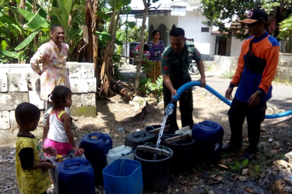 Danpos Koramil Grabagan Serma Asykur distribusikan air bersih kepada warga di Tuban. (Foto: Dok.Penrem)