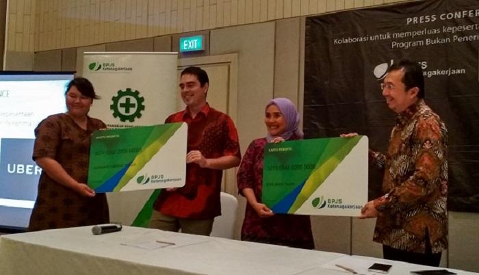 (dari kiri-kanan) John Colombo, Head of Public Policy and Government Affairs Uber Indonesia dan E. Ilyas Lubis, Direktur Perluasan Kepesertaan dan Hubungan Antar Lembaga BPJS Ketenagakerjaan memberikan simbolis kartu peserta BPJS pada dua mitra pengemudi Uber, Evie Tavipi dan Azzahra Sabrina, yang menandakan keikutsertaan mereka dalam program Jaminan Sosial Peserta Bukan Penerima Upah (BPU). Foto Istimewa/ NusantaraNews