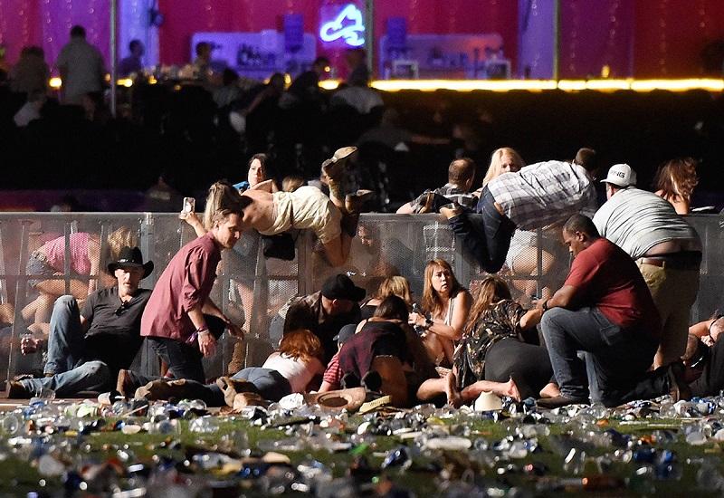 Para penonton konser musik country di Las Vegas berlindung dari tembakan. (David Becker/Getty Images)