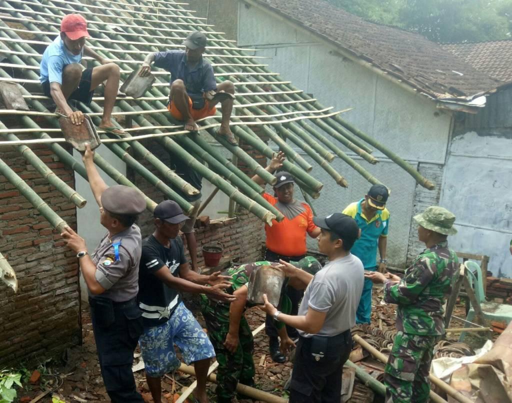 Babinsa Sempusari, Jember bersama polisi, warga dan karang taruna perbaiki rumah warga yang tertimpa pohon. Foto: Sis/Istimewa