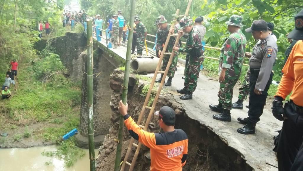 Anggota Kodim 0803 Madiun, Polres Madiun, BPBD (Badan Penanggulangan Bencana Daerah) dan Masyarakat Bersama sama kerja bhakti membuat tanggul sementara agar jalan bisa dilalui, Kamis (16/11). Foto: Arief Safuan/NusantaraNews