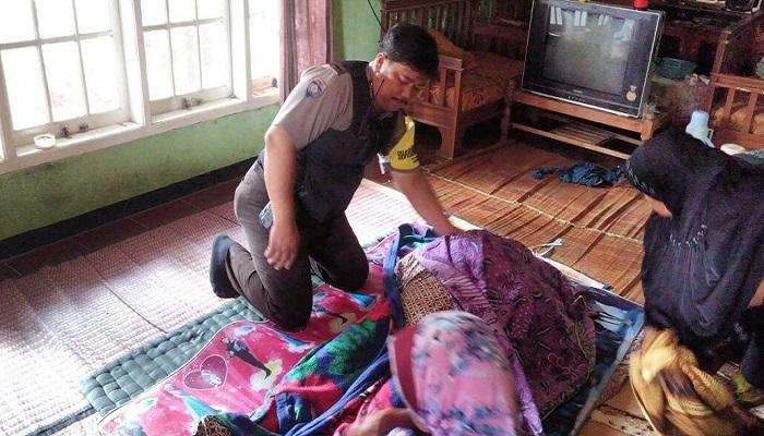 Seorang petugas polisi sedang memeriksa jenazah nenek Apong yabg tewas bunuh diri di Purwakarta. Foto: Fuljo/NusantaraNews