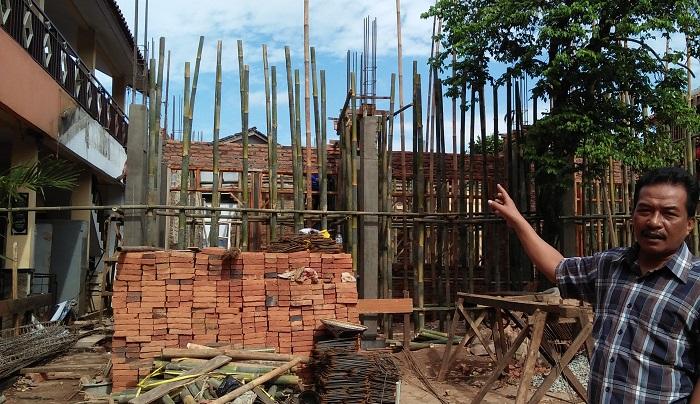 Ratiman ketua panitia proyek pengerjaan ruang fisik di SMK Putnawarman Purwakarta sedang menunjukan lokasi proyek yang menelan anggaran APBN Pusat senilaj Rp 230 juta. Foto Fuljo/ NusantaraNews