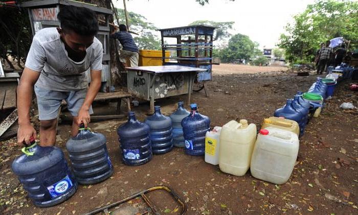 Seorang warga menata galon untuk diisi air bersih di Kawasan Manggarai, Jakarta, Minggu (8/11). Ratusan warga di RW 10 Manggarai Selatan harus antre untuk mengisi air bersih karena tidak ada pasokan air bersih melalui PDAM yang telah terjadi hampir selama dua bulan. ANTARA FOTO/Wahyu Putro