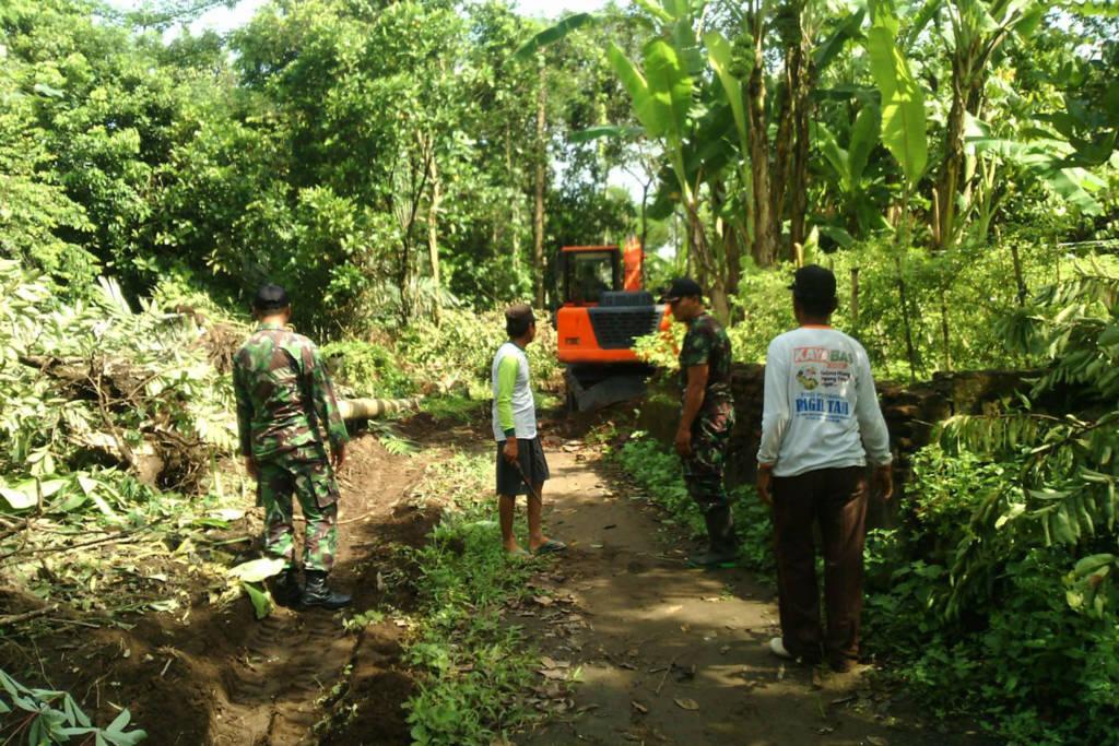 Anggota Kodim 0808 Blitar Babinsa Serda Prayitno membantu masyarakat membangun jalan. Foto: Amrin/Dok. Kodim Blitar