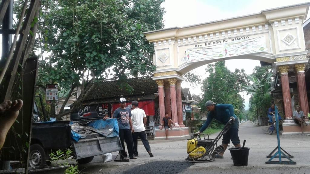 Petugas Dinas Pekerjaan Umum (PU) Pemkab Ponorogo melakukan perbaikan sementara atau penambalan jalan berlubang di sepanjang Jalan Raya Ngasinan-Bungkal, Kamis (11/1/2017). Foto: Muh Murcholis/NusantaraNews
