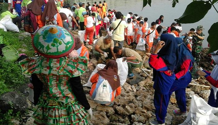 Warga masyarakat dan prajurit Korem Bhaskara Jaya membersihkan sekitar jembatan Suramadu, Jawa Timur. (Foto: Istimewa)