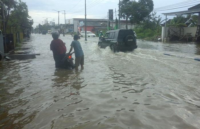 Warga menerobos banjir di Jalan Trunojoyo Sumenep. (Foto: Kafi Hidayat/NusantaraNews)