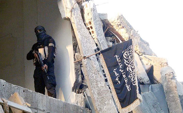 Seorang teroris bersenjata di antara reruntuhan puing-puing