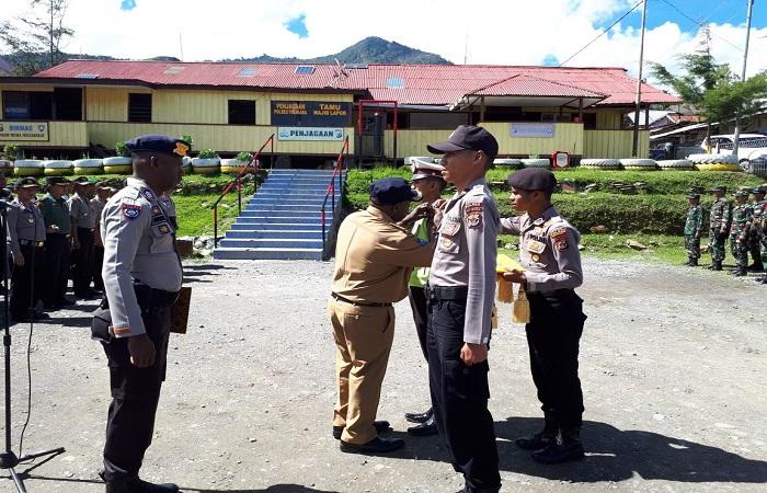 Bupati Tolikara memberikan penyematan tanda pita operasi kepada 2 perwakilan Bintara Bripda Chandra Harianto (Ba. Lantas) dan Bripda Arianto Salurapa (Ba. Sabhara). (Foto: Kasrim/NusantaraNews)