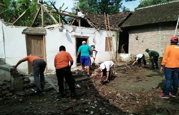 Babinsa, Polsek Jiwan, Muspika Jiwan dan BPBD Kabupaten Madiun serta warga sekitar Desa Teguhan membersihkan rumah warga yang roboh akibat diterjang angin puting beliung. (Foto: Istimewa)
