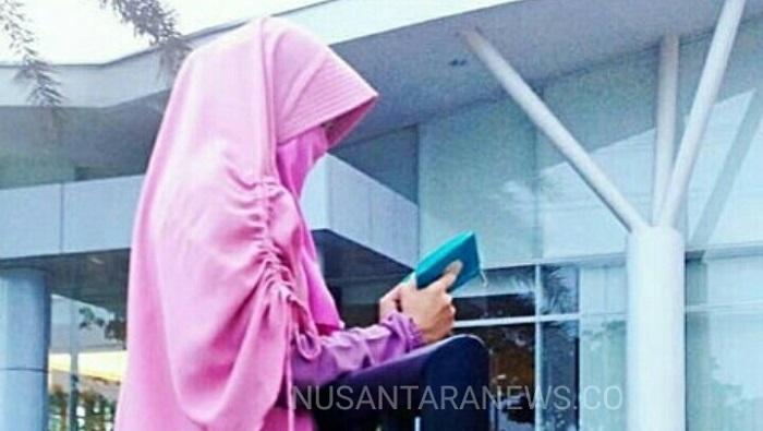 Perempuan Bercadar sedang membaca kitab suci Al-Quran kala senja. (FOTO: NUSANTARANEWS.CO/IG:DL)