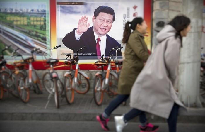 Poster Presiden Cina Xi Jinping ini ditempel di Beijing pada tanggal 2 Maret 2018. (Foto: Mark Schiefelbein/AP Photo)