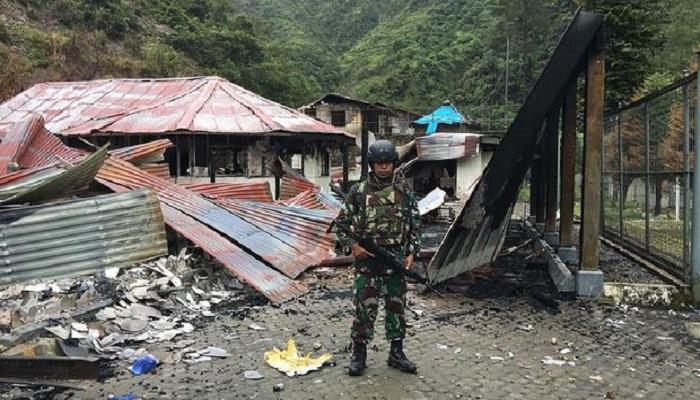 Prajurit TNI berjaga-jaga di dekat sebuah bangunan yang dibakar oleh kelompok Tentara Pembebasan Nasional Papua Barat (TPNPB). (Foto: Puspen Kodam XVII/Cendrawasih)