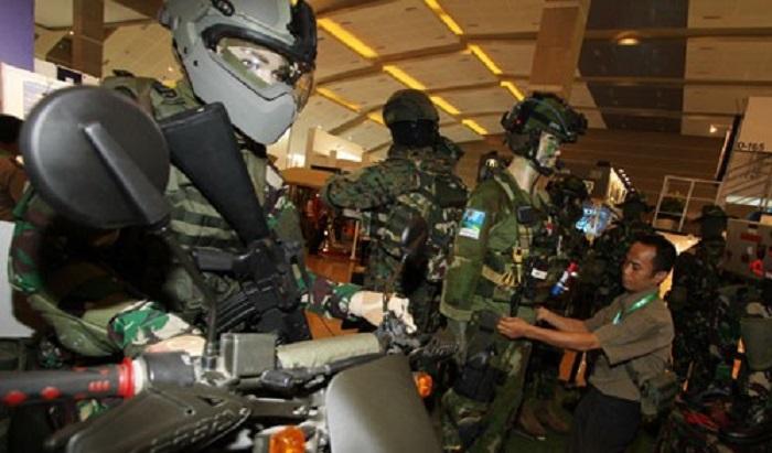 Petugas merapikan susunan pakaian anti peluru pada Indo Defence Expo 2014 di JIEXPO Kemayoran, Jakarta, Rabu (5/11/2014). (ANTARA FOTO/M. Agung Rajasa)
