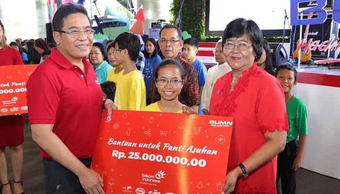 Direktur Utama Telkom Alex J. Sinaga (kiri) menyerahkan simbolis santunan kepada perwakilan penerima bantuan dari Panti Asuhan dalam acara BUMN Berbagi Bersama Panti Asuhan di Kawasan The Telkom Hub Jakarta, Sabtu (15/12). (Foto: Istimewa)