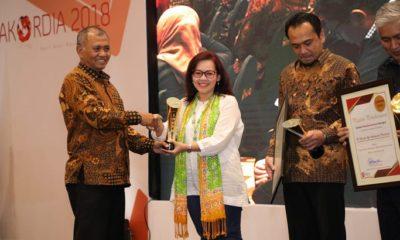Ketua KPK Agus Rahardjo (paling kiri) menyerahkan penghargaan kepada Telkom sebagai Instansi dengan Penerapan Laporan Harta Kekayaan Penyelenggara Negara (LHKPN) Terbaik Tahun 2018 kepada Senior Advisor Direktorat Human Capital Management Telkom Dian Purwaningrum (tengah) pada event Peringatan Hari Antikorupsi Sedunia (Hakordia) 2018 di Jakarta, Rabu (5/12). (FOTO: Dok. Telkom)