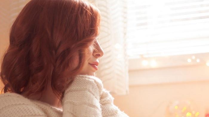 Seorang perempuan tersenyum di sebuah pagiyang cerah dan bahagia. (FOTO: Dok. GettyImage)