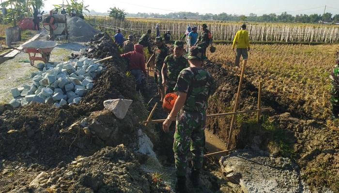 Bangun Talud Jalan, Prajurit TNI manunggal Bersama Masyarakat Ponorogo. (FOTO: NUSANTARANEWS.CO/ Muh Nurcholis)
