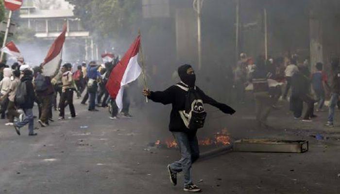 Seorang Pelajar STM Lari Membawa Bendera Merah Mutih Saat Ikut Demo Menolak Revisi UU KPK. (Foto Dok. CNN Indonesia)