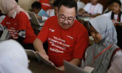 """Komisaris Utama Telkom Rhenald Kasali (tengah) memberikan pelatihan internet dasar kepada salah satu siswi Sekolah Dasar dalam program pelatihan keterampilan usaha dan pendidikan masyarakat """"IndiHome untuk Indonesia"""" di Desa Wukirsari, Bantul, Yogyakarta, Senin (9/12)."""