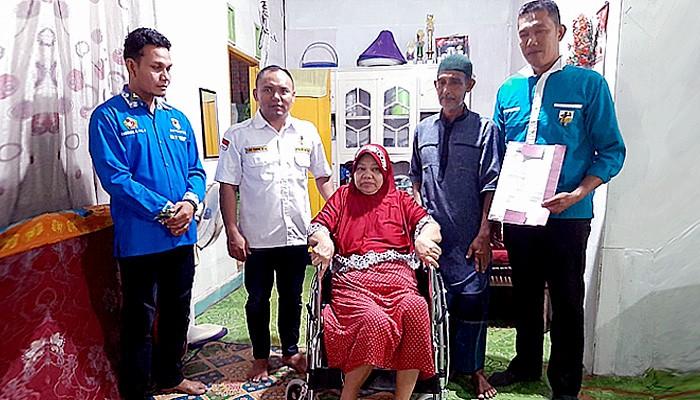 Teuku Syahwal Ketua DPD KNPI Pidie serahkan kursi roda bagi keluarga miskin.