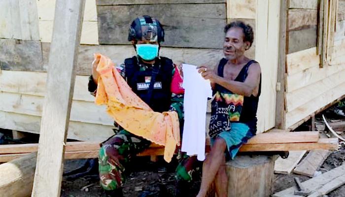 Peduli masyarakat, Satgas Pamtas Yonif Mekanis 512/QY bagikan pakaian.